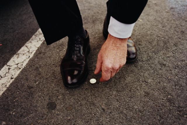 мужчина в костюме поднимает маленькую монету с дороги